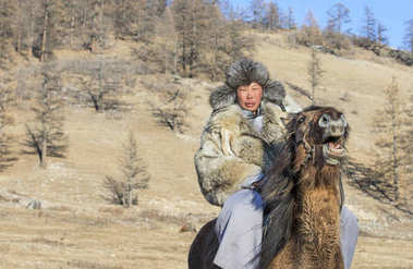 mongolian man wearing a wolf skin jacket, riding his horse in a forest
