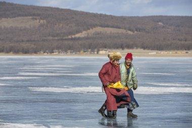 Hatgal, Mongolia, 1st March 2018: mongolian men in traditional clothing walking on frozen lake Khovsgol