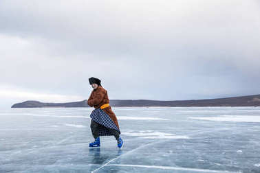 Hatgal, Mongolia, 4th March 2018: mongolian man dressed in traditional clothing skating on a frozen lake Khuvsgu