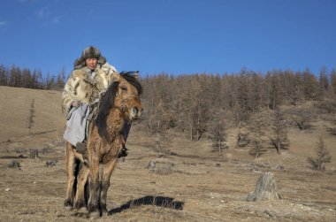 mongolian man wearing a wolf skin jacket, riding his horse in a steppe in Northern Mongolia