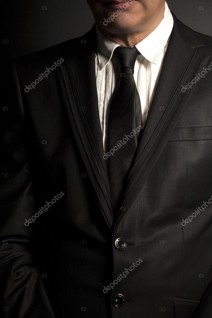 Hombre en traje negro y corbata negra sobre un fondo negro — Foto de Stock 2f5ccc478c9