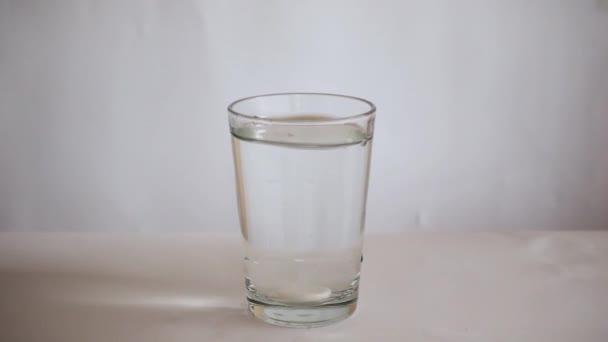 Droga padá do sklenice vody a začíná se rozpouštět