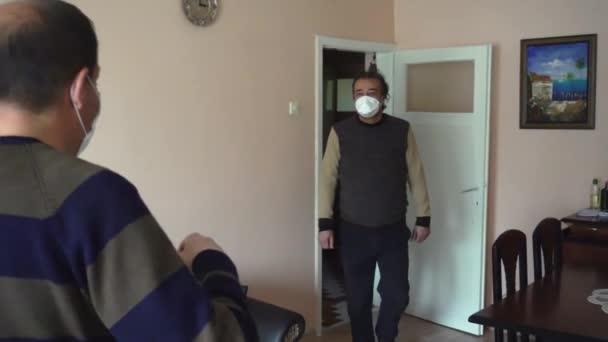 Turečtí bratři s maskami narážejí loktem jeden do druhého, aby doma zpomaleně zabránili viru korony.
