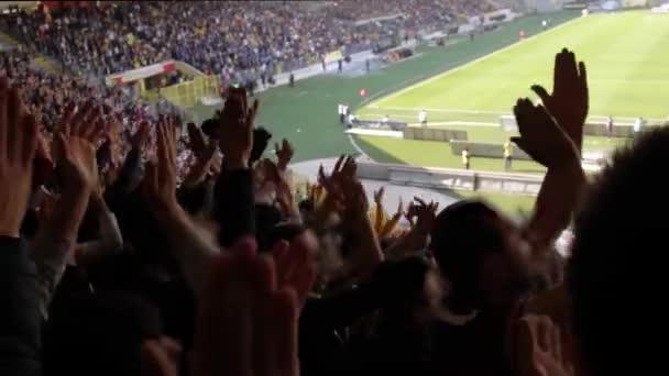 A szurkolók szurkolnak és támogatják a labdarúgó klubjukat a stadionban a bajnoki meccsen egy napsütéses napon.