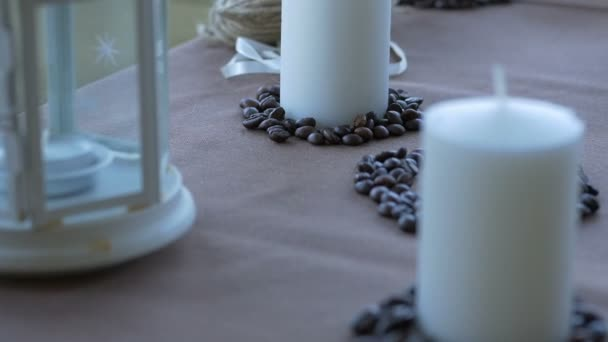 white candles and grains of coffee are on a brown table