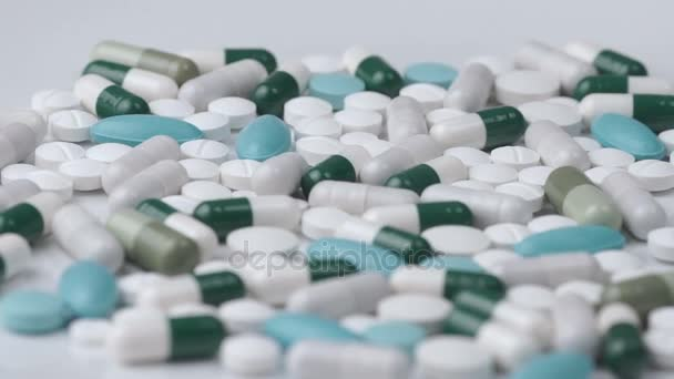 White green pills rotate on a white background