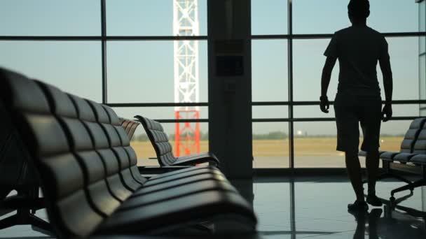 Mann kommt und steht in voller Höhe, blickt aus dem Fenster des Flughafenterminals, Silhouette