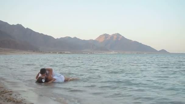 Mladý pár objímat a líbat, ležící v moři