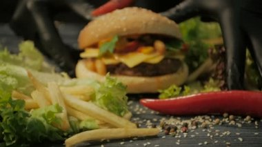 Tasty burger is great on a wooden tray. A man takes his hands, dolly shot