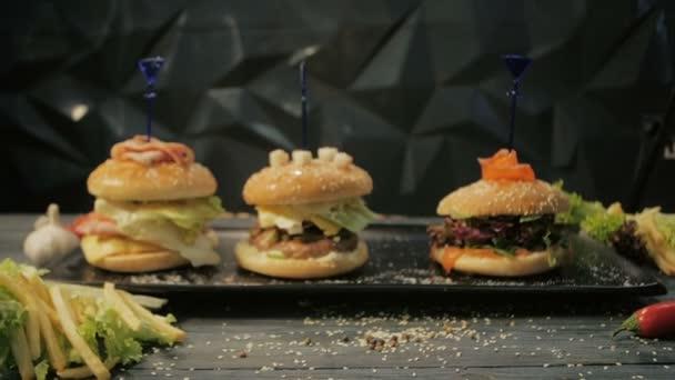 Impostare hamburger con pesce, carne e verdure. Vista dallalto. Su un fondo di legno, dolly shot