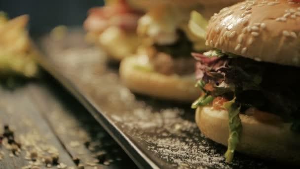 Hamburger se slaninou s šťavnaté hovězí a čerstvý salát ingredience na rustikální dřevěný stůl. Detailní záběr