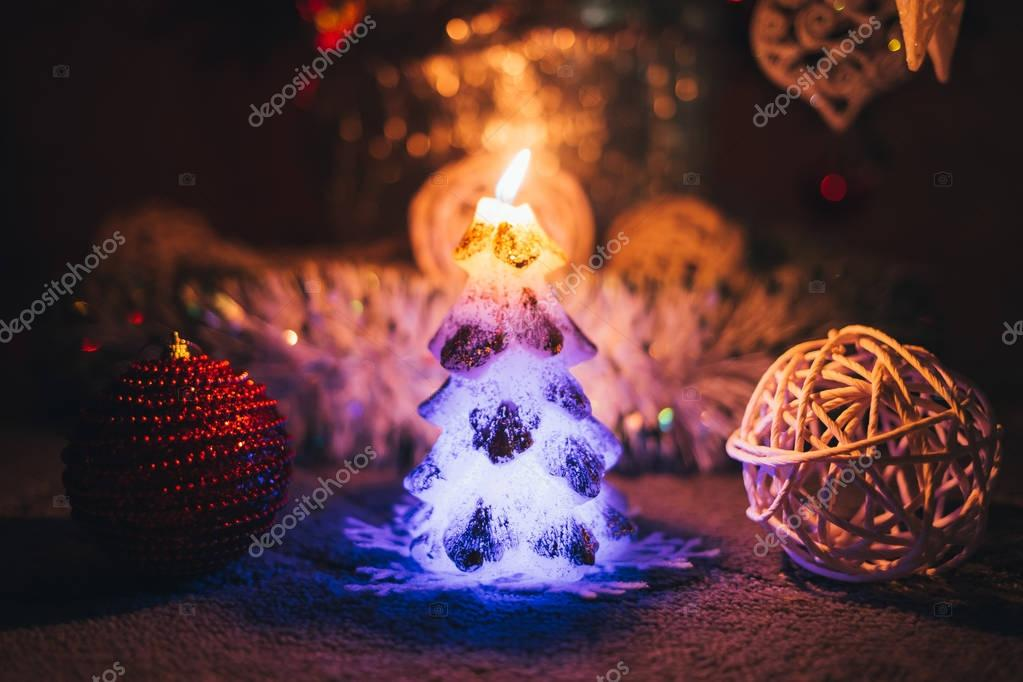 Candle and toys near Christmas tree