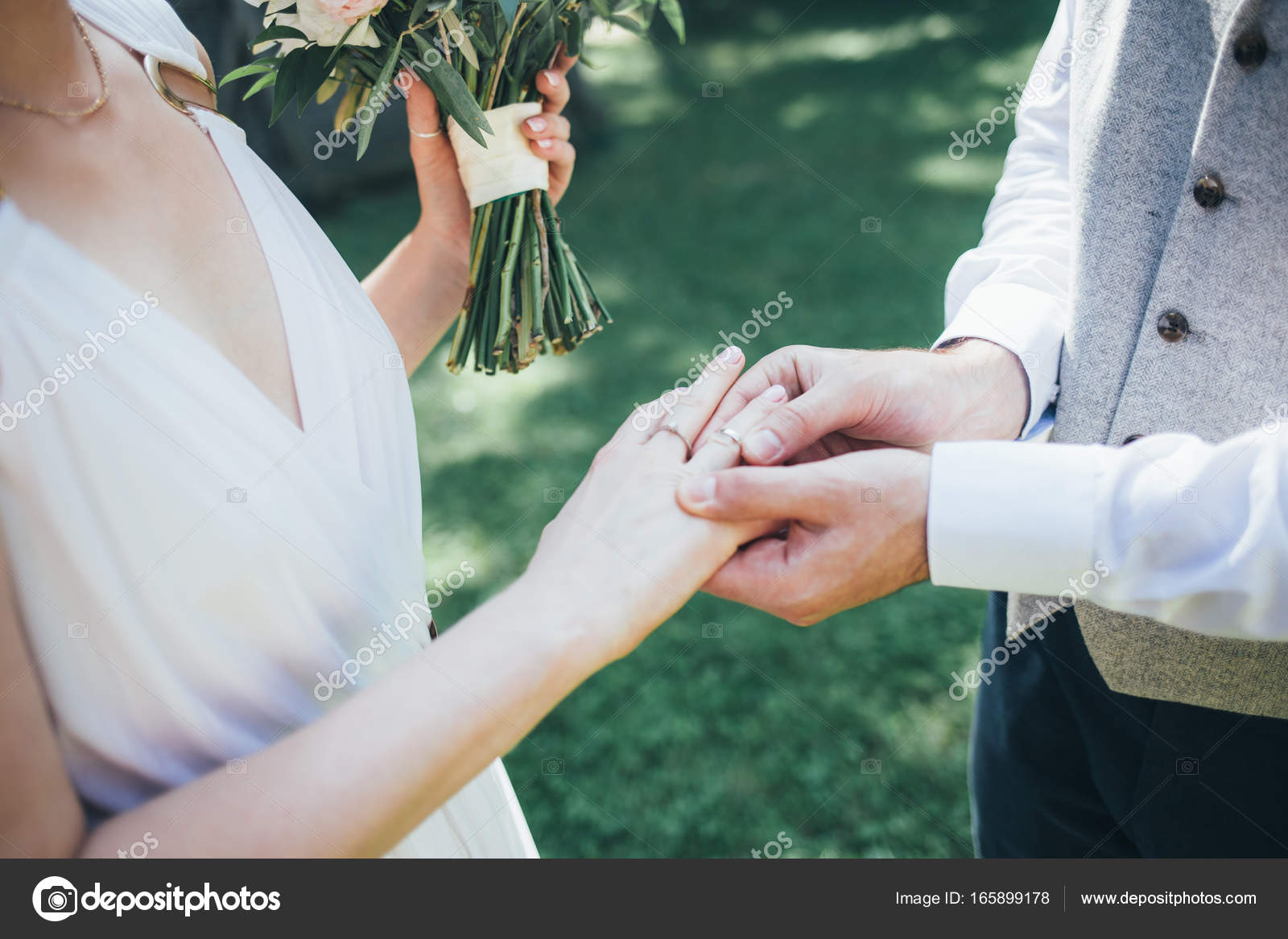 Groom wearing wedding ring on finger of bride Stock Photo