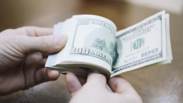 Ruce počítání amerických dolarových bankovek nebo placení v hotovosti na peněžním pozadí.