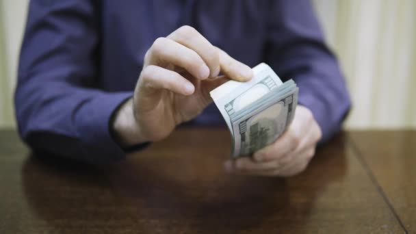 A rich man holds a pack of dollars in his hands and counts large sums of money