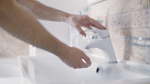 Közelről férfi kezet mosni szappan nélkül a fürdőszobában. Reggeli rutinhigiénia