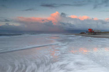beach of Petten Netherlands during sunset and strong wind, a piece of art in the sand