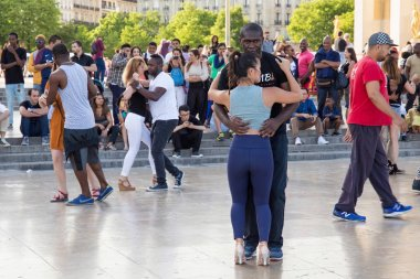 Unknown young people dancing on the Place de Trocadero.