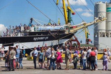 Tourists near the famous barque Kruzenshtern (prior Padua) moored in the pier of Kaliningrad Sea Port.