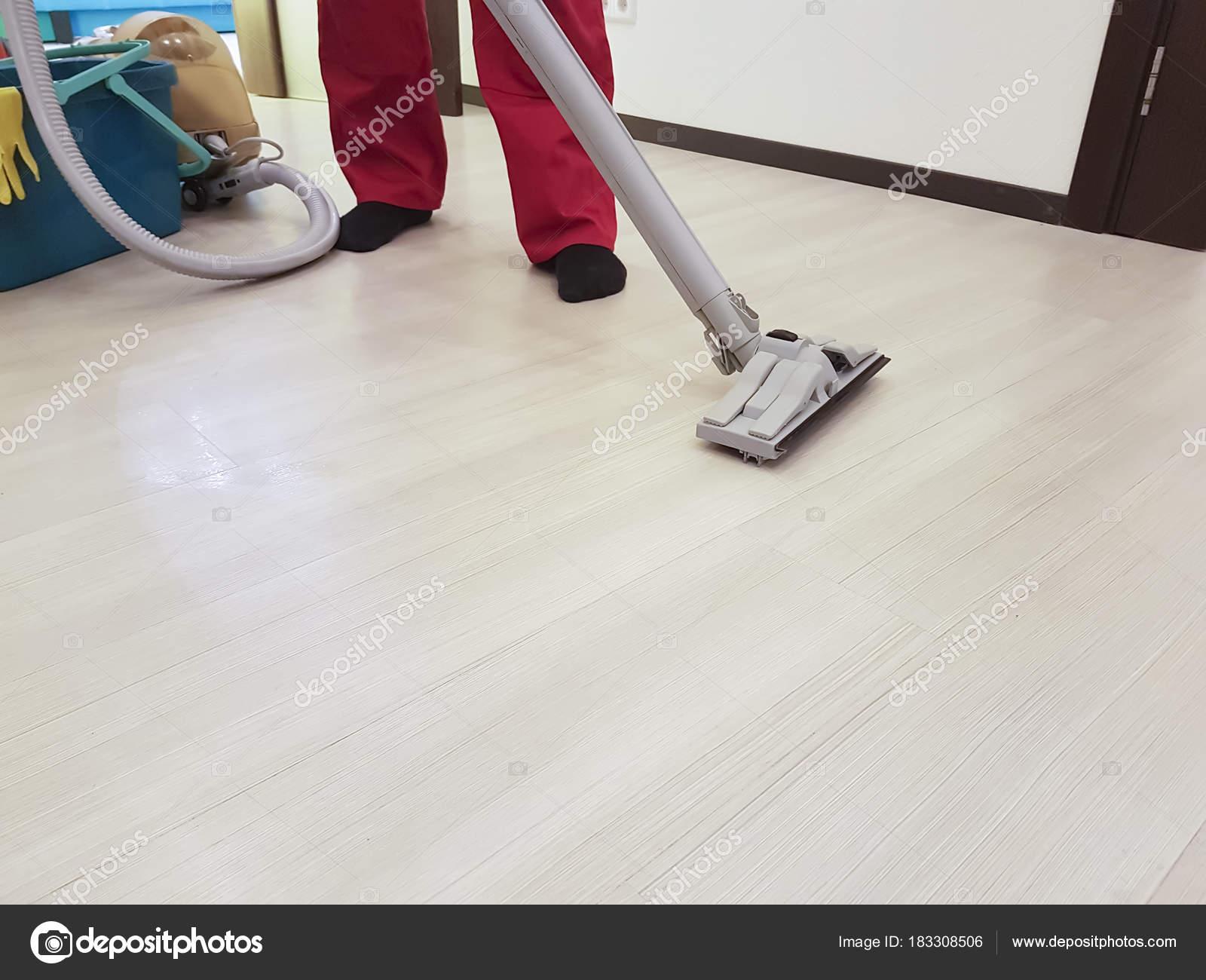 090eee3478f Ο υπάλληλος της εταιρείας αφαιρεί τη βρωμιά από το πάτωμα με μια ηλεκτρική σκούπα  ατμού στο διαμέρισμα — Εικόνα από ...