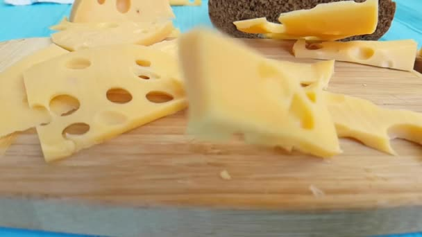 cheese Swiss on a wooden chalkboard pieces, drops, slow-motion shot