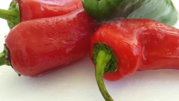 červené a zelené papriky na bílém pozadí, nalití vody