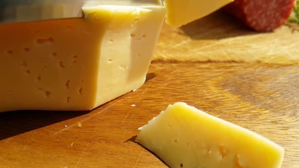cheese cut with a knife on a wooden, slow-motion shot