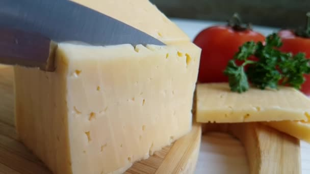 knife slicks cheese on a wooden, slow-motion shot