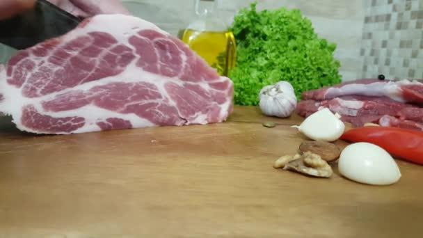 Schneiden von saftigen und köstlichen Schweinehals auf dem Hintergrund von Butter, Walnüssen, Zwiebeln, Gemüse und Pfeffer