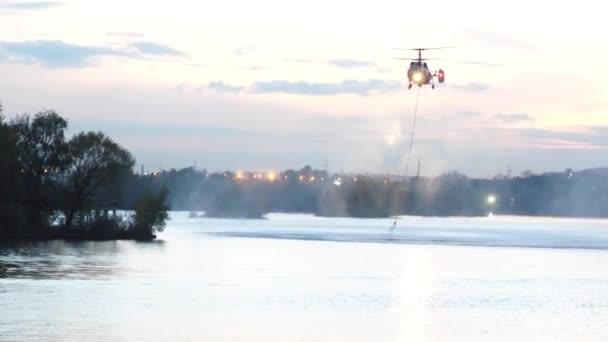 Vrtulník sbírá vodu v řece hasit požár. Záchranná služba a hasiči požár uhasit. Vrtulník se vznášel ve vzduchu. Hašení nebezpečný požár ve městě