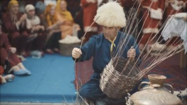 An adult man in a national costume is weaving a basket. An old Muslim is weaving a basket of twigs. National holiday in the east. A man in a mountain where there are many ginshin Muslim women. Weave