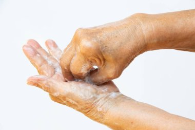 Senior woman's hands washing her hands using soap foam in step 6 on white background, Close up & Macro shot, Selective focus, Prevention from covid19, Bacteria, healthcare concept, 7 step wash hand