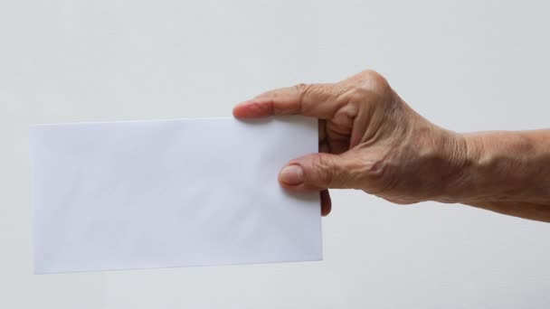 Idős nő jobb kéz tartó fehér boríték vagy menyasszony elszigetelt fehér háttérrel, közelkép és makró lövés, Üzleti koncepció