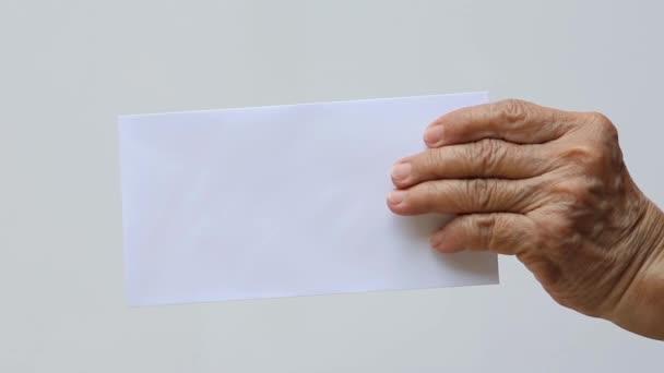 Pravá ruka starší ženy drží bílou obálku nebo nevěstu izolované na bílém pozadí, zblízka a makro záběr, obchodní koncept