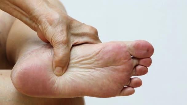 Seniorin mit Schmerzen im linken Fuß, Massage mit der Hand vor weißem Hintergrund, Nahaufnahme  Makroaufnahme, asiatischer Körperteil, Gesundheitswesen, Über Massagekonzept