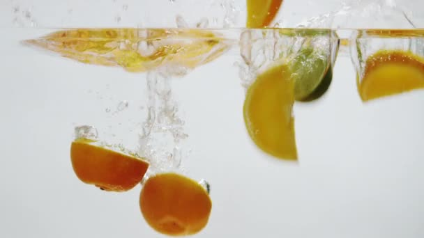 Oranges and limes falling into water