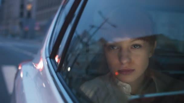 Frau schaut durch ein Fenster und trinkt Kaffee