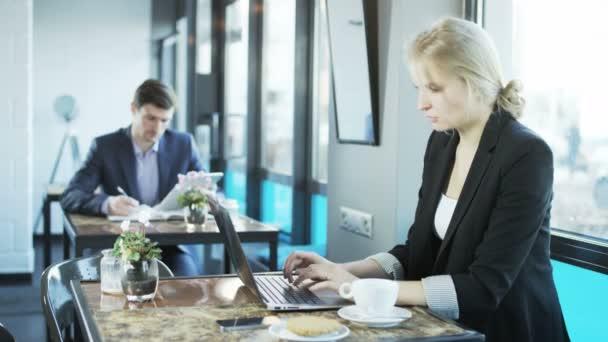 Člověk je psaní, žena používá přenosný počítač. Přestávka na oběd. Střílel na Red Epic