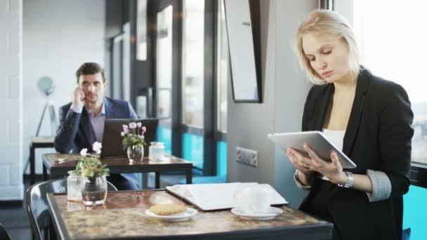 Die junge Frau schreibt und benutzt einen Tablet-Computer. Mittagspause. Schuss auf rotes Epos