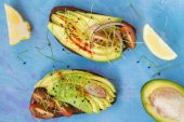 Sandwiches with avocado, sprouts, tomato, blue background, top v