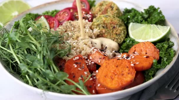 Quinoa-Salat mit gebackenen Süßkartoffeln, Falafel, Grünkohl und Erbsensamen gießen.