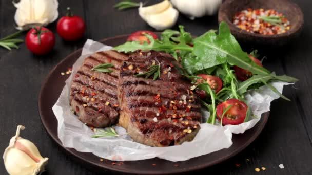 Grilované hovězí steaky s rukolou a rajčatovým salátem na dřevěném talíři, posypané kořením, tmavé pozadí.