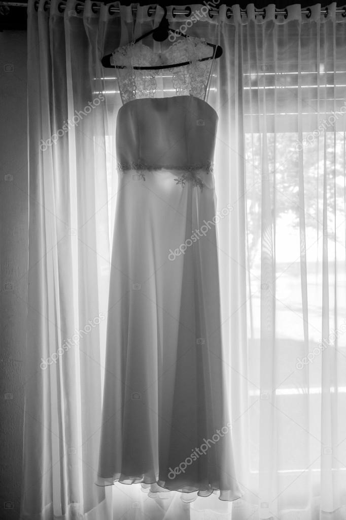 vestido de novia blanco de casamiento colgado en una percha de ventana habitacin con cortinas de la madre un contra luz blanco y negro