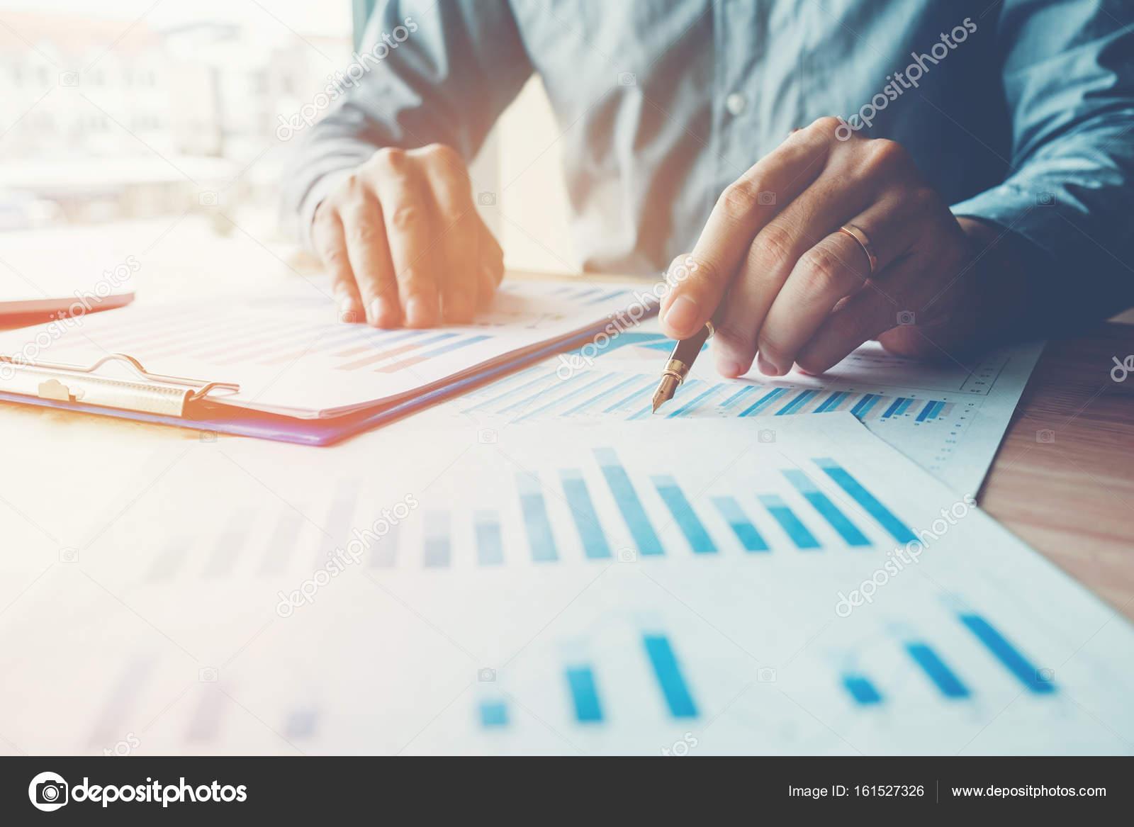 Business-Mann hält Stift auf zusammenfassende Berichte Diagramme ...