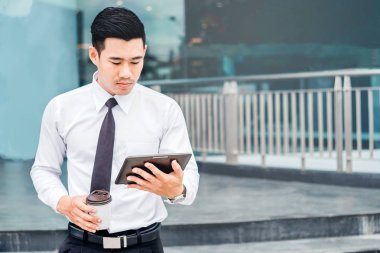 Businessman  With Coffee Using Digital Tablet at city outside of