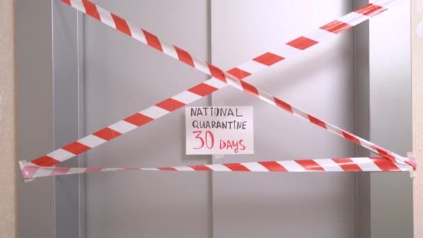 Vörös-fehér jelzőszalag és aláírás a felirattal Nemzeti karantén 30 nap lóg a lift ajtaján