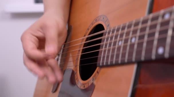 muž hrající doma na akustickou kytaru. Řetězce prstů a akordy s mediátorem