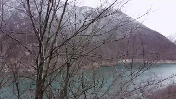Beautiful landscape with snowy mountains and pond through branches of tree. River or lake valley in the foothills in winter.