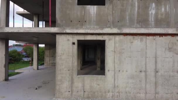 Kamera pomalu stoupá z prvního patra na střechu podél fasády nedokončených výškových budov, stavební jeřáb na pozadí. Rozvoj infrastruktury v rezidenční části města.