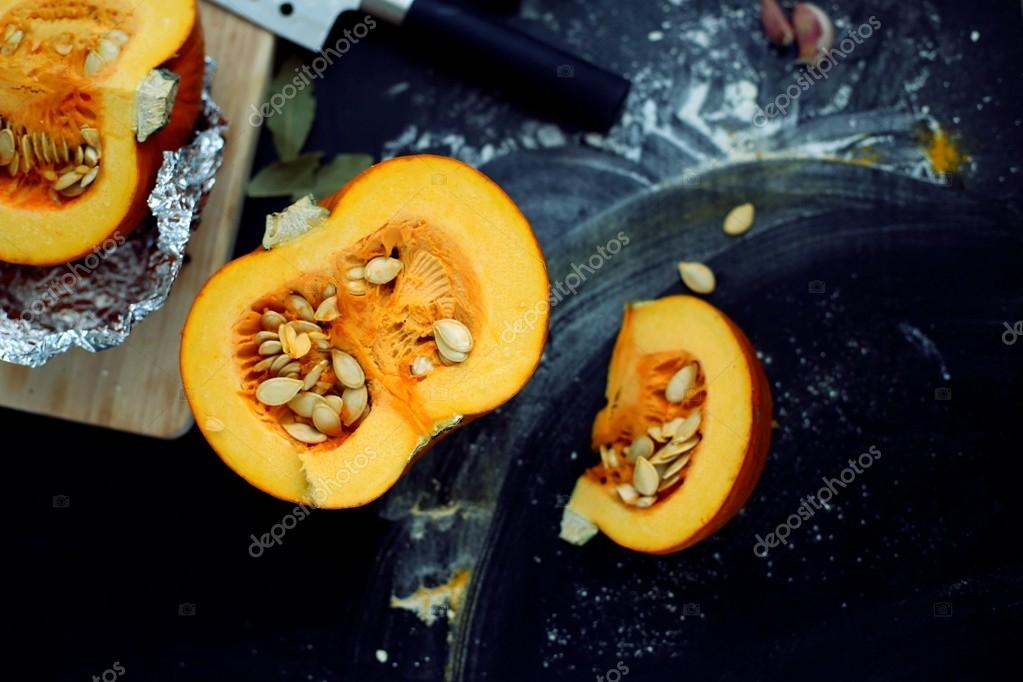 Fresh pumpkin slice on a black wooden table with flour texture. Autumn cooking background. Healthy eating. Top view.